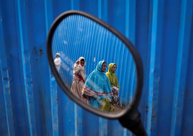 Dawoodi Bohra Muslims are reflected in the rear mirror of a parked scooter as they walk past the site of an under construction mosque in Mumbai, India, September 19, 2016. (Photo by Danish Siddiqui/Reuters)