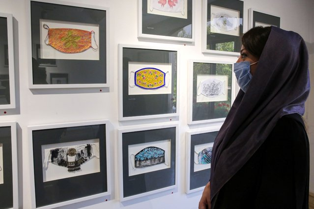 An Iranian woman looks at mask-themed artworks on display at an art exhibit in Cama gallery in the capital Tehran on August 1, 2020, during the COVID-19 pandemic. (Photo by Atta Kenare/AFP Photo)