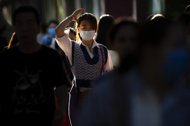 A woman wearing a face mask to protect against the coronavirus is caught in the sunlight as she walks along a street in Beijing, Friday, September 18, 2020. Even as China has largely controlled the outbreak, the coronavirus is still surging across other parts of the world. (Photo by Mark Schiefelbein/AP Photo)