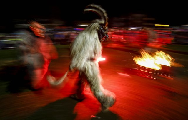 A man dressed in a traditional Perchten costume and mask performs during a Perchten festival in the western Austrian village of Huben November 22, 2014. (Photo by Dominic Ebenbichler/Reuters)