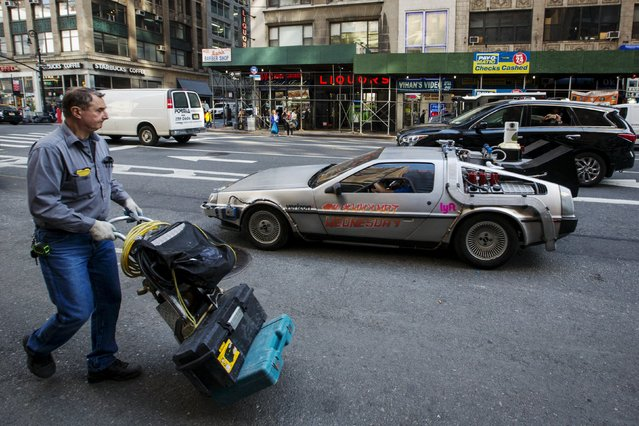 """A worker walks past a DeLorean Motor Company DMC-12 customized to look identical to the car used in the film """"Back to the Future Part II"""" and that will be part of a Lyft promotion in New York, October 21, 2015. (Photo by Lucas Jackson/Reuters)"""