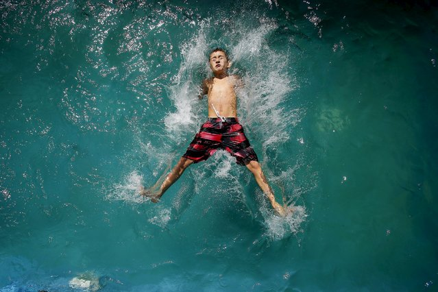 A child plays in a pool during a warm sunny day in Santiago, March 22, 2015. (Photo by Ivan Alvarado/Reuters)