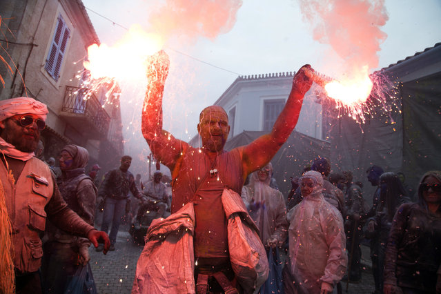Revelers throw flour as they participate in the flour war, a unique colorful flour fight marking the end of the carnival season, in the port town of Galaxidi, some 200 kilometers (120 miles) west of Athens, Monday, February 19, 2018. (Photo by Petros Giannakouris/AP Photo)