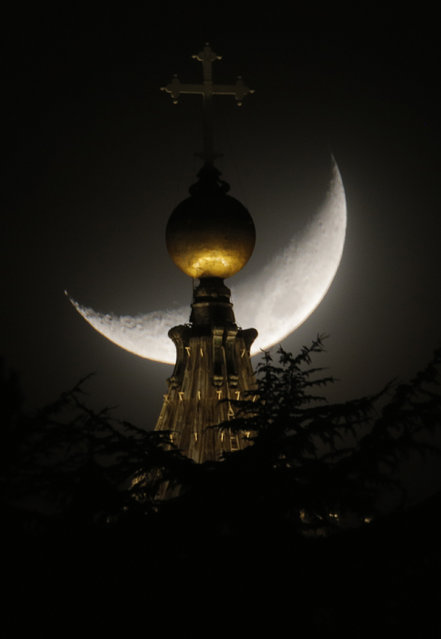 """The moon is seen behind a dome of St. Peter's Basilica at the Vatican, Saturday, March 16, 2013. Pope Francis offered intimate insights Saturday into the moments after his election, telling journalists that he was immediately inspired to take the name of St. Francis of Assisi because of his work for peace and the poor – and that he himself would like to see """"a poor church and a church for the poor"""". (Photo by Dmitry Lovetsky/AP Photo)"""