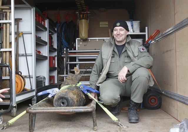Joerg Neumann of the German bomb disposal team poses next to a diffused unexploded World War II bomb near to the main station in Berlin April 3, 2013. Rail services to and from the capital were disrupted and residents were evacuated from their houses following the discovery of an unexploded 100 kilo World War II bomb near to the rail tracks of the Hauptbahnhof, during routine checks on Tuesday, local media reported. (Photo by Tobias Schwarz/Reuters)