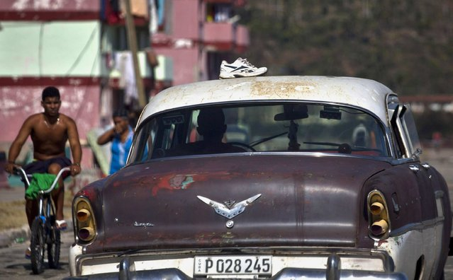 A man drives his American classic car while air-drying his sneakers soaked by the heavy rains caused by Hurricane Matthew, in Baracoa, Cuba, Friday, October 7, 2016. (Photo by Ramon Espinosa/AP Photo)