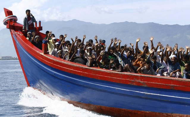 Ethnic Rohingya refugees from Myanmar wave as they are transported by a wooden boat to a temporary shelter in Krueng Raya in Aceh Besar April 8, 2013. About 74 Rohingya refugees, who were heading for Australia, were found stranded on Aceh island by Indonesian fishermen on Sunday, a police official said on Monday. (Photo by Junaidi Hanafiah/Reuters)