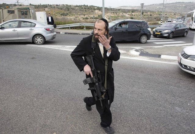 An Israeli Ultra-Orthodox Jewish man run at the scene where a Palestinian attacked civilians with a chemical substance near the West Bank Jewish settlement of Neve Daniel, part of the Gush Etzion bloc, December 12, 2014 A Palestinian man threw a chemical substance believed to be acid at an Israeli family in the occupied West Bank on Friday, injuring a man and four children, Israeli police and the military said. The assailant was shot and wounded immediately after the attack, which took place at a checkpoint south of Jerusalem. (Photo by Ronen Zvulun/Reuters)