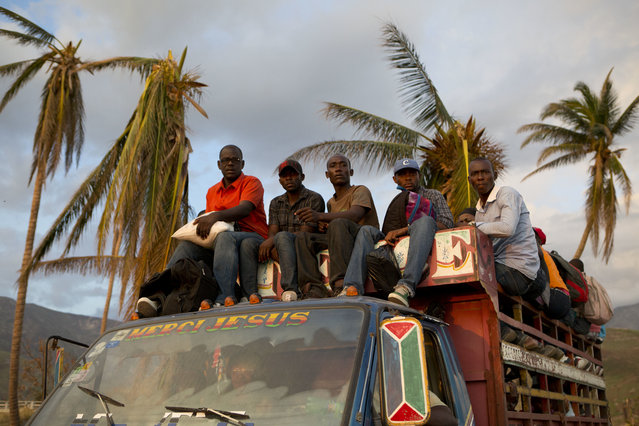 Residents ride atop a passenger transport truck as they prepare to ford one of many rivers who's bridges were washed out along the southern coast road, after the passing of Hurricane Matthew, in Port-a-Piment, Haiti, Monday, October 10, 2016. A week after the storm smashed into southwestern Haiti, some communities along the southern coast have yet to receive any assistance, leaving residents who have lost their homes and virtually all of their belongings struggling to find shelter and potable water. (Photo by ebecca Blackwell/AP Photo)