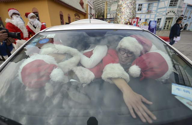 Staff dressed as Santa Claus try to squeeze into a car at a theme park in Changsha, December 18, 2014. (Photo by Reuters/China Daily)