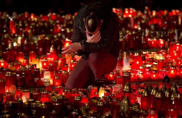 Un hombre se arrodilla en medio de un altar conmemorativo por las personas que fallecieron en un incendio en el club nocturno Colectiv, en Bucarest, Rumania, el viernes 6 de noviembre de 2015. Decenas de personas fallecieron y 180 resultaron heridas por el incendio del 30 de octubre. (Photo by Vadim Ghirda/AP Photo)