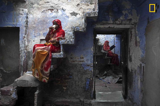 """These Rajasthani sisters were sitting on the staircase inside their house relaxing and enjoy a cup of masala chai"". (Photo by Firdaus Hadzri/National Geographic Travel Photographer of the Year Contest)"