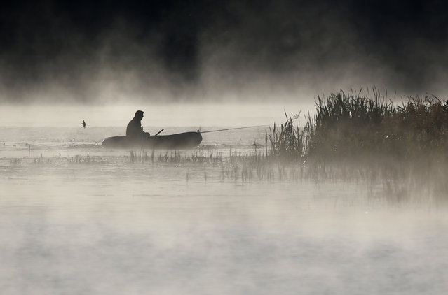 A man fishes from his boat as fog rises over the lake in the town of Logoisk, 40 kms. (25 miles) north of Minsk, Belarus, Thursday, September 15, 2016. (Photo by Sergei Grits/AP Photo)