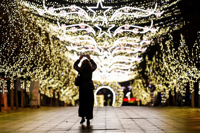 A woman takes pictures using her mobile phone on a deserted square decorated ahead of Christmas, in Pristina on December 7, 2020, during a government-imposed curfew from 7pm to 5am, as part of preventive measures against the spread of the Covid-19. (Photo by Armend Nimani/AFP Photo)
