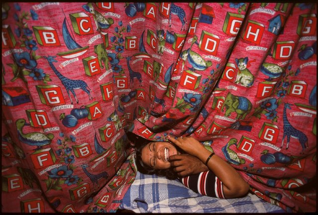 Kamla behind curtains with a customer, Falkland Road, Bombay, India, 1978. (Photo by Mary Ellen Mark)
