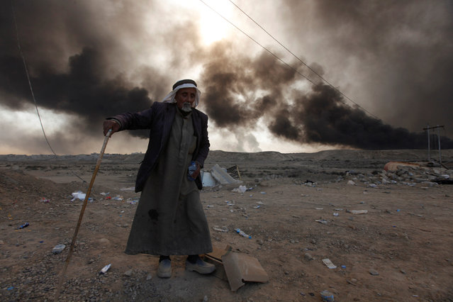A man returns to his village after it was liberated from Islamic State militants, south of Mosul in Qayyara, Iraq, October 22, 2016. The fumes in the background are from oil wells that were set ablaze by Islamic State militants. (Photo by Alaa Al-Marjani/Reuters)