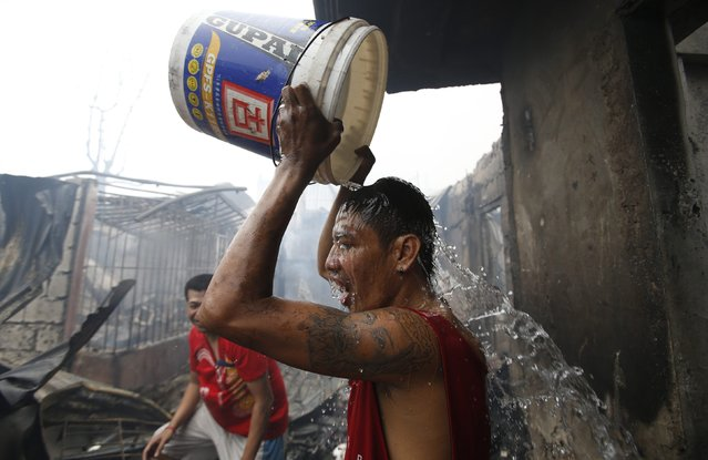 A man douses himself with a bucket of water outside the remains of his house gutted by a fire at a slum colony in Quezon city, Metro Manila January 1, 2015. (Photo by Erik De Castro/Reuters)