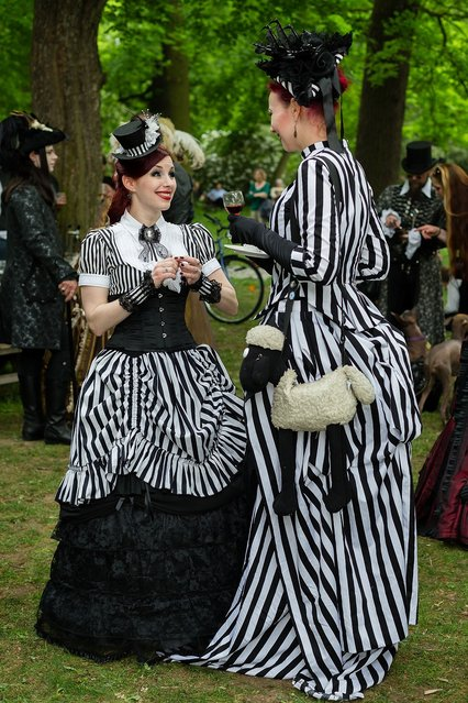 Two women in Victorian clothing and with a shawn-the-sheep-bag chat during the traditional park picnic on the first day of the annual Wave-Gotik Treffen, or Wave and Goth Festival, on May 17, 2013 in Leipzig, Germany. The four-day festival, in which elaborate fashion is a must, brings together over 20,000 Wave, Goth and steam punk enthusiasts from all over the world for concerts, readings, films, a Middle Ages market and workshops. (Photo by Marco Prosch)