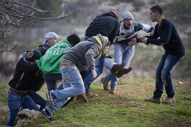 Palestinians carry an injured man during clashes with Israeli soldiers outside the Ofer military prison near the West Bank city of Ramallah on Friday, January 2, 2015. (Photo by Majdi Mohammed/AP Photo)