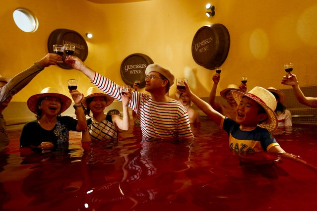 People clink wine glasses as they stand in a hot bath with coloured water representing wine at the Hakone Kowaki-en Yunessun spa resort during an event marking Beaujolais Nouveau Day in Hakone west of Tokyo, November 19, 2015. (Photo by Thomas Peter/Reuters)