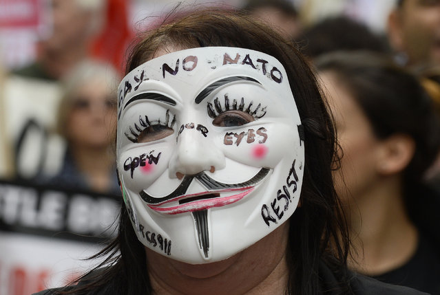 Wales: A demonstrator wearing a Guy Fawkes mask takes part in an anti-war protest march in Newport, Wales, August 30, 2014. (Photo by Rebecca Naden/Reuters)