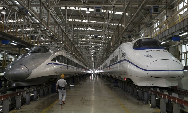 A worker walks between two bullet trains at a high speed railway maintenance station in Xi'an, Shaanxi province, China, in this September 10, 2015 file photo. (Photo by Reuters/Stringer)