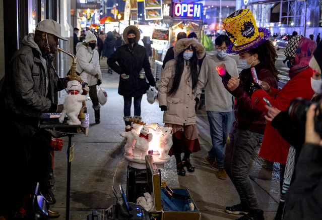 Pedestrians pass by and also watch street entertainment on Eighth Avenue, adjacent to a closed-off Times Square in New York, late Thursday, December 31, 2020, as celebrations have been truncated this New Year's Eve due to the ongoing pandemic. (Photo by Craig Ruttle/AP Photo)