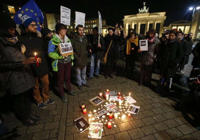 People gather to mourn for the victims in front of the Brandenburg Gate near the French embassy at Pariser Platz in Berlin January 7, 2015, following a shooting by gunmen at the offices of weekly satirical magazine Charlie Hebdo in Paris. (Photo by Fabrizio Bensch/Reuters)