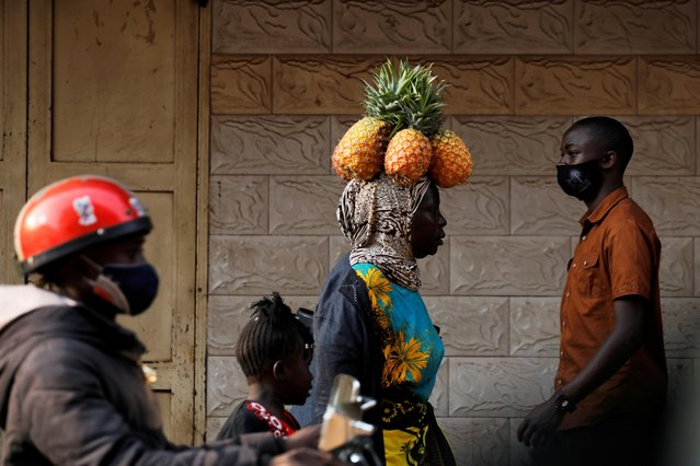 A woman walks while carrying pineapples on her head on a street in Kampala, Uganda on January 12, 2021. (Photo by Baz Ratner/Reuters)