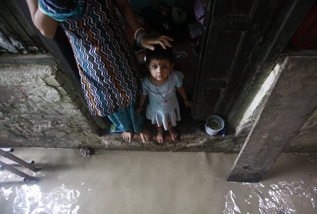 A child watches while standing on the doorstep of her house next to a flooded alley due to rising water level of river Yamuna after heavy monsoon rains in New Delhi June 18, 2013. The rains are at least twice as heavy as usual in northwest and central India as the June-September monsoon spreads north, covering the whole country a month faster than normal. (Photo by Anindito Mukherjee/Reuters)