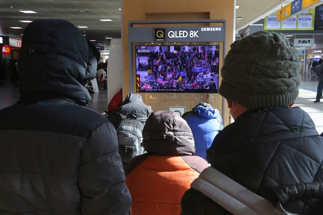 People watch a TV screen showing the news on a violent mob that loyal to U.S. President Donald Trump stormed the U.S. Capitol, at the Seoul Railway Station in Seoul, South Korea, Thursday, January 7, 2021. (Photo by Ahn Young-joon/AP Photo)