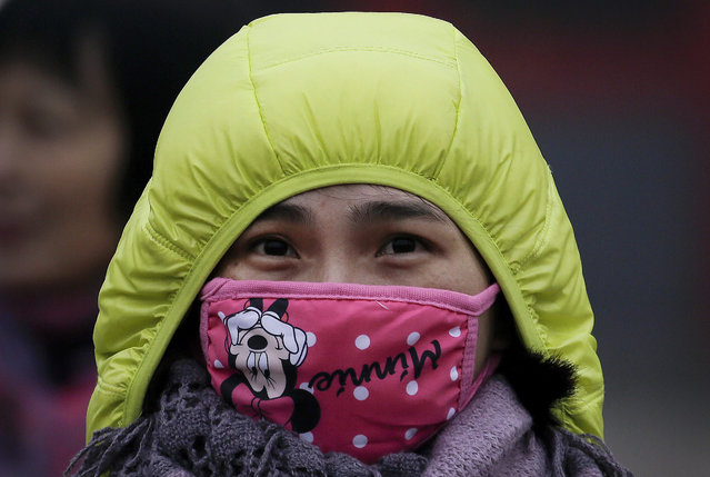 In this December 8, 2015 photo, a woman wears a mask to protect herself from pollutants near the Forbidden City on a heavily polluted day in Beijing. (Photo by Andy Wong/AP Photo)