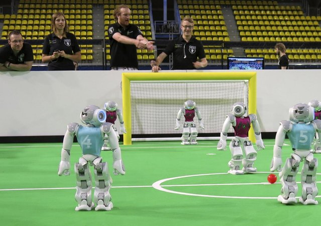 "Robots in the ""standard platform"" division prepare for kickoff at a match held during the RoboCup championships in Eindhoven, Netherlands on Thursday, June 27, 2013. Around 300 teams from 40 countries are competing this week in the RoboCup championships. The competition has the long-term goal of building a team of androids good enough to beat the human world cup team by 2050. (Photo by Toby Sterling/AP Photo)"