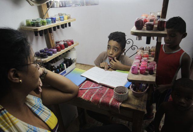 A mother helps her son with his homework at their home, which she also uses as a nail salon, in Havana January 20, 2015. (Photo by Reuters/Stringer)