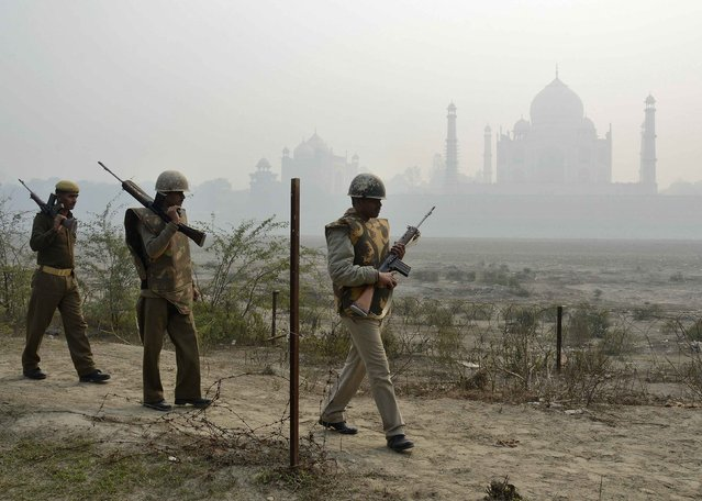 Indian security personnel patrol on the rear side of the historic Taj Mahal, on a foggy winter day in the northern Indian city of Agra, January 17, 2015. (Photo by Brijesh Singh/Reuters)