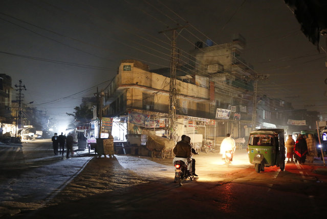 People are silhouetted on vehicles headlights on a dark street during widespread power outages in Rawalpindi, Pakistan, Sunday, January 10, 2021. Pakistan's national power grid experienced a major breakdown late night on Saturday, leaving millions of people in darkness, local media reported. (Photo by Anjum Naveed/AP Photo)
