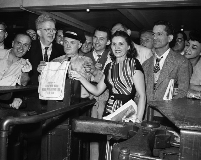 Carmen Gherdol of Long Island City, N.Y. drops the last nickel permitted to be dropped in one of the BMT-IRT subway turnstiles at Times Square, New York, June 30, 1948 when the fare was raised to ten cents for a subway ride in New York City. Assistant supervisor Bartholomew Barry, left, prepares to pull a canvas cover over the slot, until it is changed over to receive the smaller coin. Others are unidentified. (Photo by Matty Zimmerman/AP Photo)