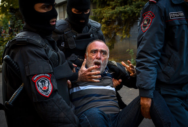 Armenian police officers detain a protestor during a rally against the country's agreement to end fighting with Azerbaijan over the disputed Nagorno-Karabakh region in Yerevan on November 12, 2020. Armenia on November 12, 2020 arrested 10 leading opposition figures for violently protesting against a Russian-brokered peace deal that ended weeks of fighting with Azerbaijan and sparked fury with Prime Minister Nikol Pashinyan. (Photo by Karen Minasyan/AFP Photo)