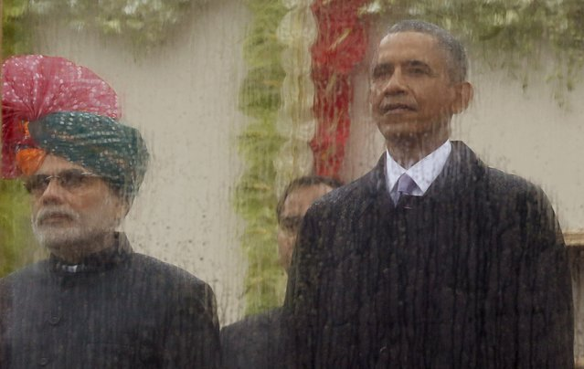 India's Prime Minister Narendra Modi (L) and U.S. President Barack Obama watch India's Republic Day parade from behind rain streaked bullet proof glass as they stand in the rain together in New Delhi January 26, 2015. (Photo by Jim Bourg/Reuters)