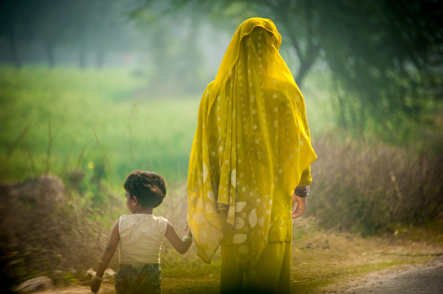 """Motherhood"". Calm Silence shared between a mother and daughter amongst the frenzied traffic along the road to Agra. Location: Somewhere between Delhi & Agra, India. (Photo and caption by Darrell Lew/National Geographic Traveler Photo Contest)"