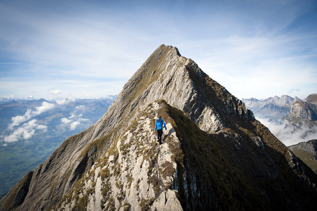 A climber walks on the ridge beneath the eastern peak of the Gamsberg (2385 meters above sea level) near Grabs, Switzerland, Friday, October 3, 2014. (Photo by Gian Ehrenzeller/AP Photo/Keystone)