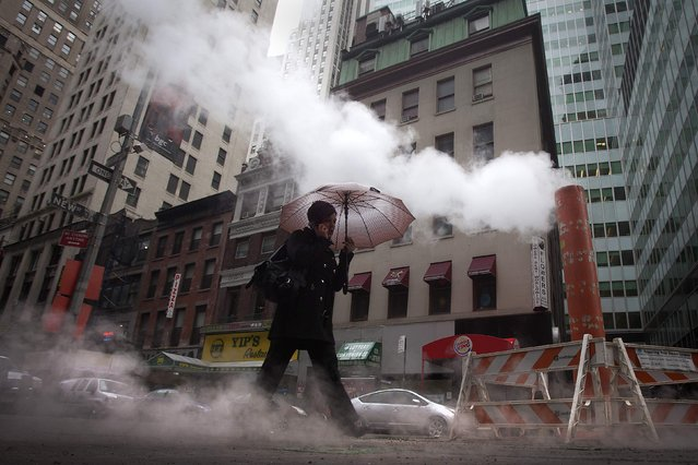 A commuter walks though steam in the Manhattan borough of New York, December 23, 2014. (Photo by Carlo Allegri/Reuters)