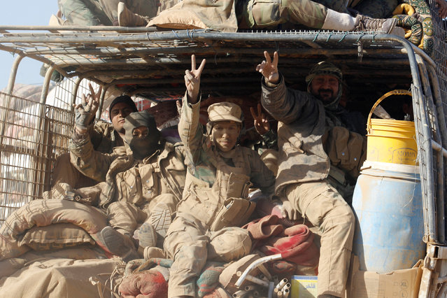 Members of the Shi'ite Badr Organisation fighters ride in a military vehicle during a battle with Islamic State militants at the airport of Tal Afar west of Mosul, Iraq, November 20, 2016. (Photo by Khalid al Mousily/Reuters)