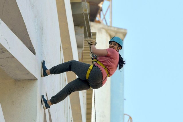 A youth rappels down the face of the Kanteerava Outdoor Stadium as part of a program held on the occasion of International Women's Day, in Bangalore on March 8, 2021. (Photo by Manjunath Kiran/AFP Photo)
