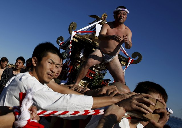"A man wearing the traditional ""fundoshi"" or loincloth rides on a ""mikoshi"" or portable shrine as local people carry it into the sea during a festival to wish for calm waters in the ocean and good fortune in the new year in Oiso, Kanagawa prefecture, west of Tokyo, Japan, January 1, 2016. (Photo by Yuya Shino/Reuters)"