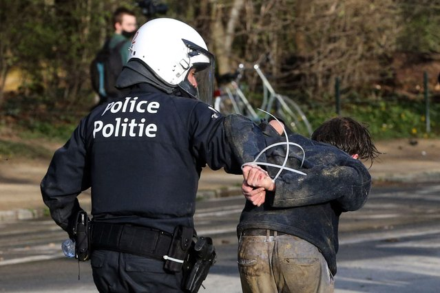 A Belgian police officer arrest a demonstrator at the Bois de la Cambre parc, in Brussels, on April 1, 2021 during a unauthorised rally, for a fake concert announced on social media as an April Fool's Day prank. Police on horseback and using a water cannon charged a crowd of thousands of people gathered in a Brussels park for a fake concert announced on social media as an April Fool's Day prank. AFP journalists at the scene saw at least one police officer injured and several people in the crowd arrested. (Photo by François Walschaerts/AFP Photo)