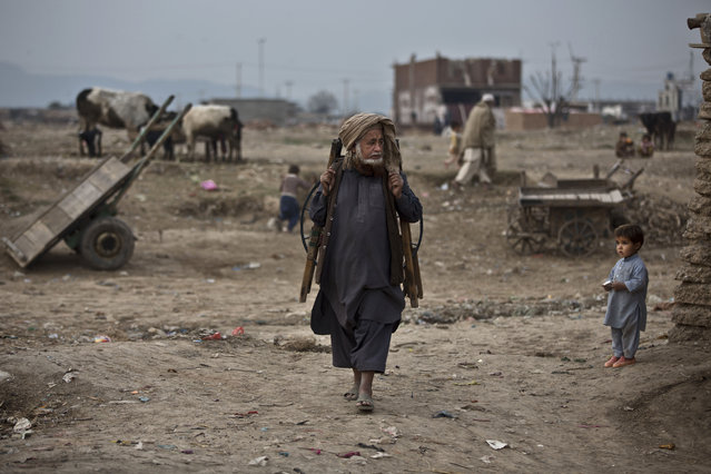 A Pakistani knife-grinder looks for customers in a slum that hosts Afghan refugees and internally displaced Pakistanis from tribal areas, on the outskirts of Islamabad, Pakistan, Friday, February 6, 2015. (Photo by Muhammed Muheisen/AP Photo)