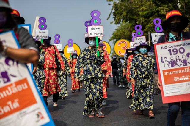 Women rally for maternity rights and workers rights while holding up signs in the shape of the number 8 to commemorate international women's day on March 08, 2021 in Bangkok, Thailand. Members of Thai labor unions and women's networks march from Democracy Monument to Government House calling for women workers rights and maternity rights on International Women's Day. The demonstration aimed to draw attention to the International Labor Organization's C190 and C183, which are laws concerning harassment and violence in the workplace and maternity protection. (Photo by Lauren DeCicca/Getty Images)