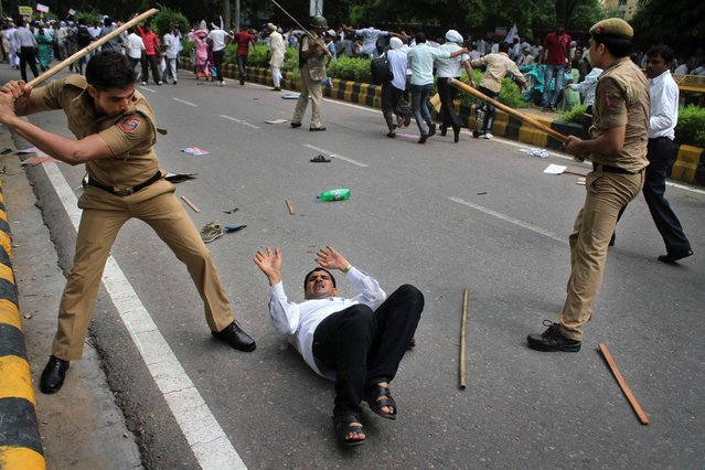 Indian police use batons to disperse a group of protestors who participate in a rally demanding caste-based affirmative action for promotions in government jobs in New Delhi, India, Monday, August 12, 2013. (Photo by AP Photo)