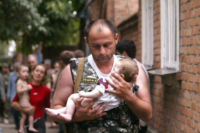 A Russian police officer carries a released baby from a school seized by heavily armed masked men and women in the town of Beslan in the province of North Ossetia near Chechnya, in this September 2, 2004 file photo. (Photo by Viktor Korotayev/Reuters)